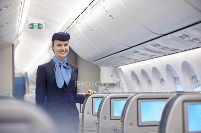 Retrato, Sonriente, seguro mujer auxiliar de vuelo en avión - foto de stock