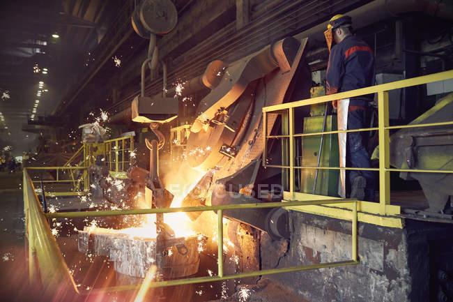 Stahlarbeiter auf Plattform über geschmolzenen Ofen im Stahlwerk — Stockfoto