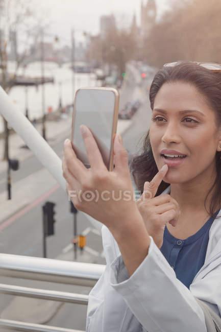 Donna che controlla il trucco con il telefono della fotocamera sul ponte urbano, Londra, Regno Unito — Foto stock