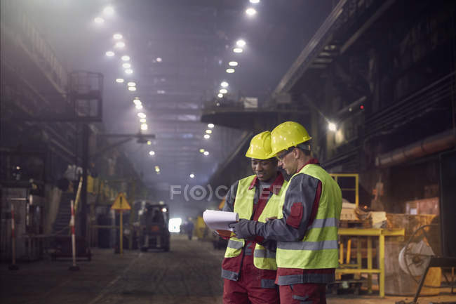 Steelworkers with clipboard meeting in steel mill — Stock Photo