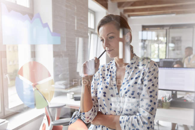 Pensive businesswoman reviewing graph and pie chart on window in office — Stock Photo