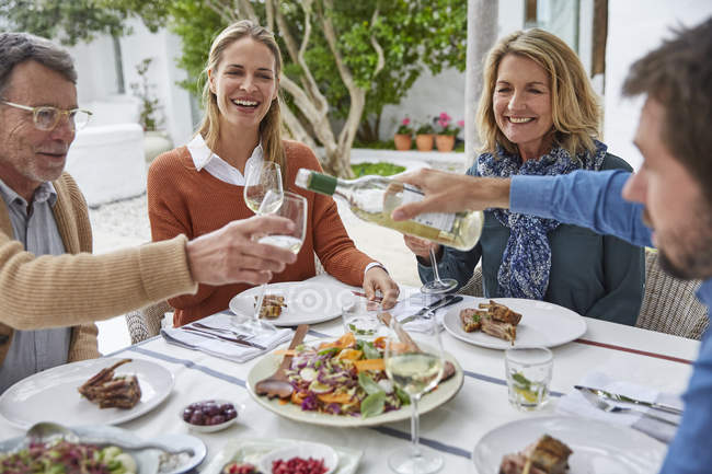 Couples drinking white wine and eating lunch on patio — Stock Photo