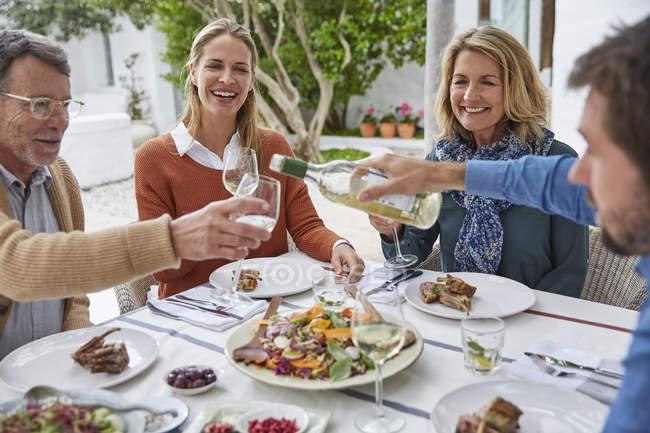 Couples, boire du vin blanc et de manger le déjeuner sur le patio — Photo de stock