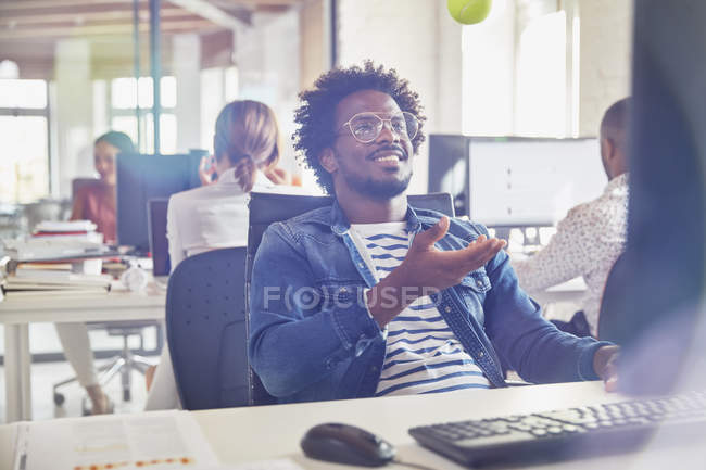 Businessman tossing tennis ball at desk in office — Stock Photo