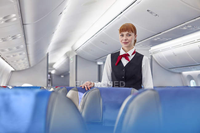 Portrait confident female flight attendant on airplane — Stock Photo