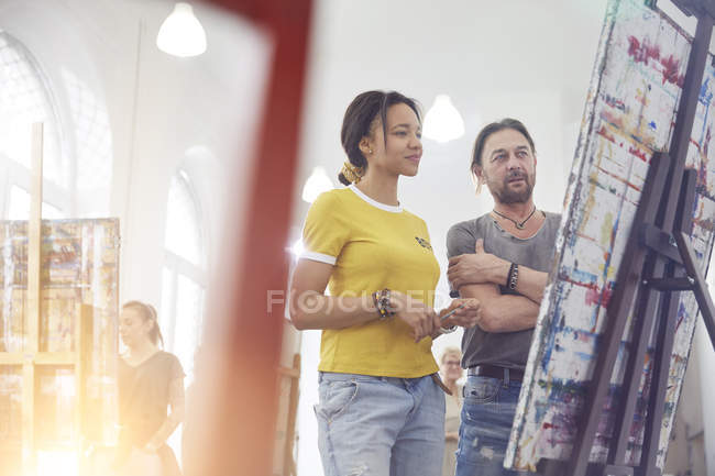 Artists looking at painting in art class studio — Stock Photo