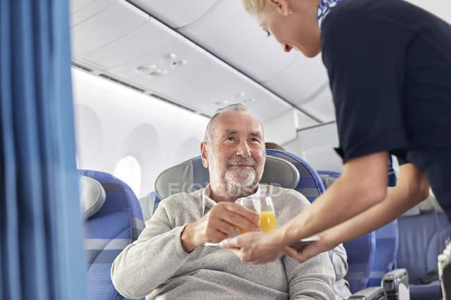 Comissária de bordo servindo suco de laranja para homem avião — Fotografia de Stock
