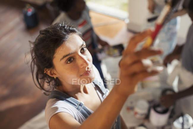 Молодая женщина, живопись на дому — стоковое фото