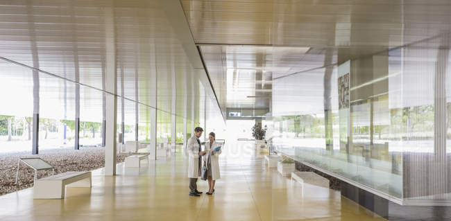 Cientistas em jalecos falando no moderno corredor do lobby do escritório — Fotografia de Stock