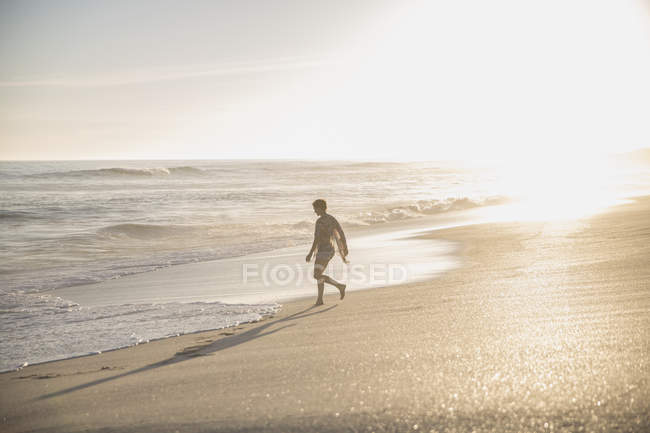 Silhouette woman walking on sunny summer ocean beach — Stock Photo