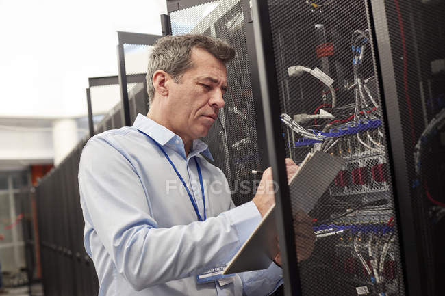Male IT technician writing on clipboard at panel in server room — Stock Photo