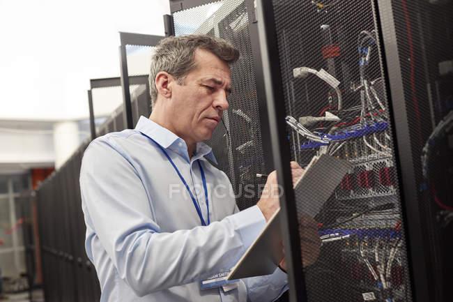 Мужчины это техник, написание на буфера обмена на панели в серверной комнате — стоковое фото