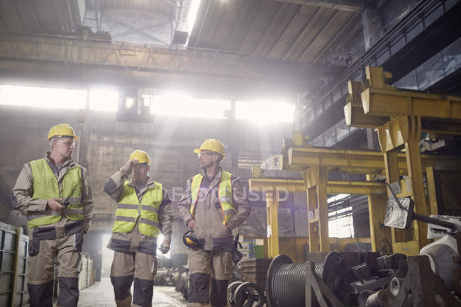 Steelworkers walking and talking in steel mill — Stock Photo