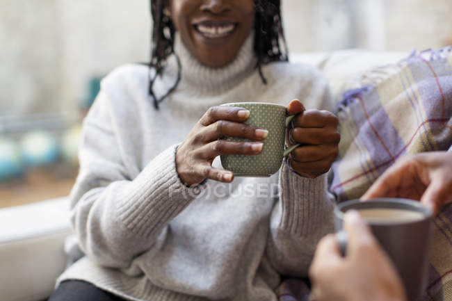 Femmes parler et boire du thé sur canapé — Photo de stock