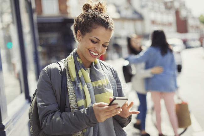 Smiling young woman texting with cell phone on sunny urban street — Stock Photo