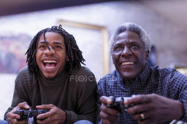 Grand-père enthousiaste et petit-fils jouer jeu vidéo — Photo de stock