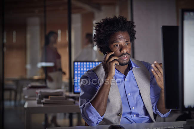 Businessman gesturing, talking on cell phone, working late at computer in dark office — Stock Photo