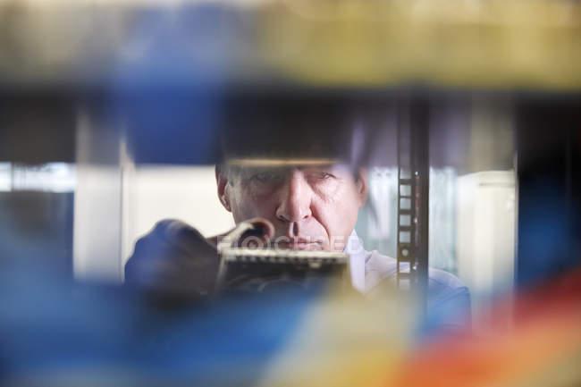 Técnico de TI masculino enfocado que trabaja en la sala de servidores - foto de stock
