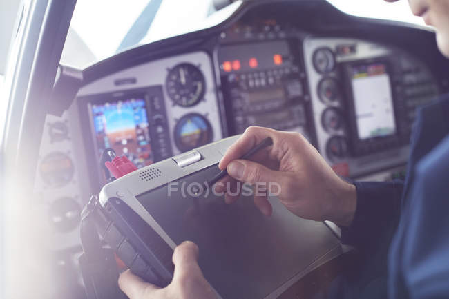 Airplane pilot using stylus on digital tablet in cockpit — Stock Photo