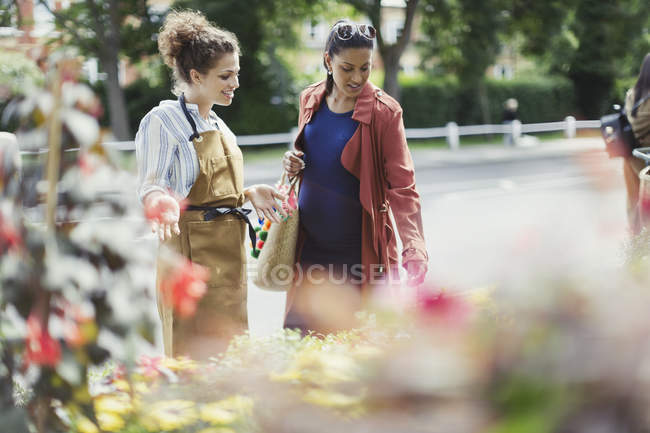 Female florist helping pregnant shopper at flower shop storefront — Stock Photo