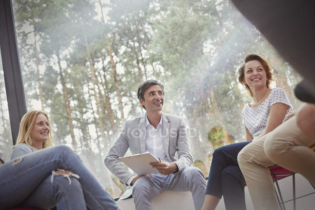 Smiling people talking in group therapy session — Stock Photo