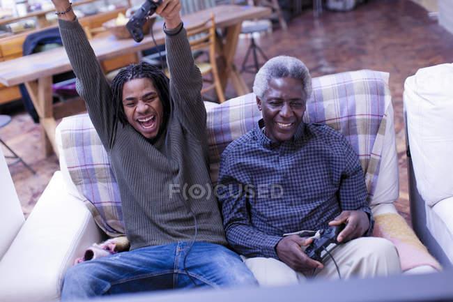 Grand-père enthousiaste et petit-fils jouer des jeux vidéo sur canapé — Photo de stock