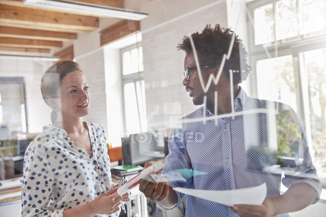 Business people with paperwork reviewing graph on glass in office — Stock Photo