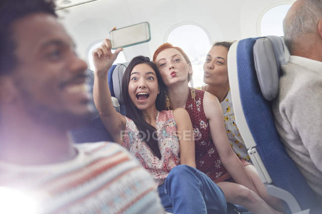 Playful young friends with camera phone taking selfie on airplane — Stock Photo