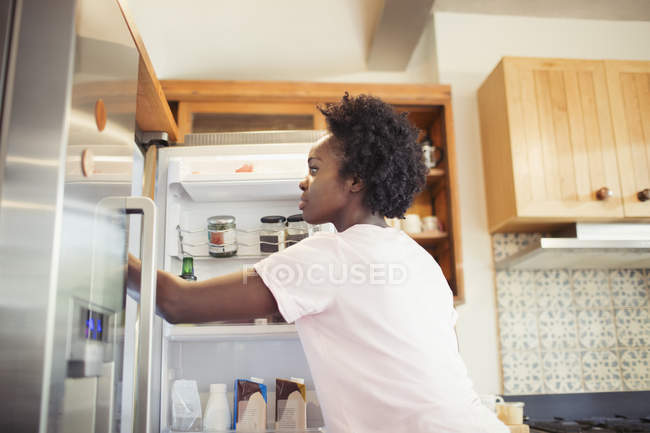 Woman reaching into refrigerator in kitchen — Stock Photo