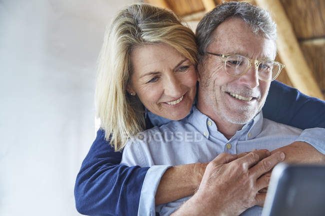 Liebespaar umarmt und benutzt Laptop — Stockfoto