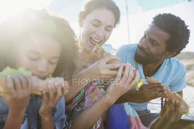 Multi-ethnic family eating baguette sandwiches on sunny beach — Stock Photo