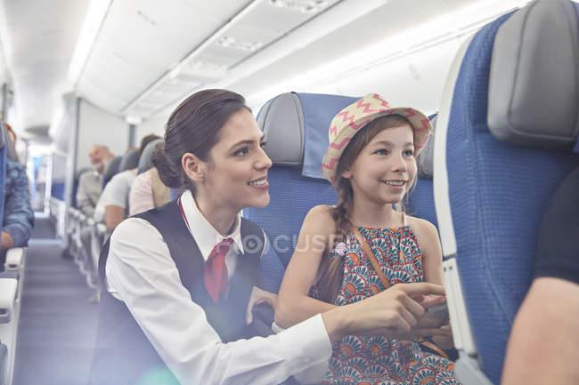 Asistente de vuelo femenino ayudando a chica a bordo de avión - foto de stock