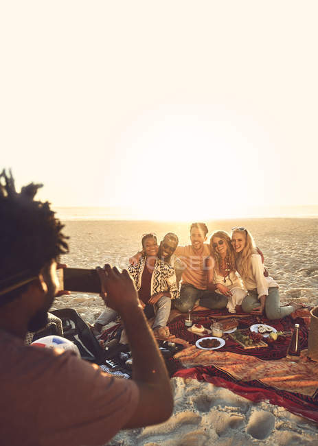 Young man with camera phone photographing friends enjoying picnic on sunny summer beach — Stock Photo