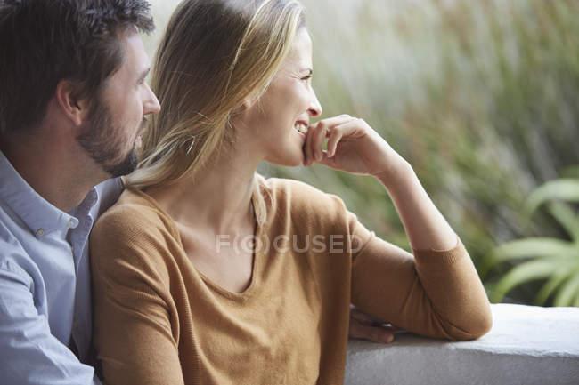 Lächelndes Paar schaut auf Terrasse weg — Stockfoto