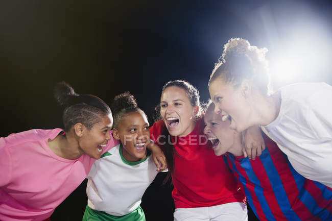 Enthusiastic young female soccer teammates celebrating, cheering in huddle — Stock Photo