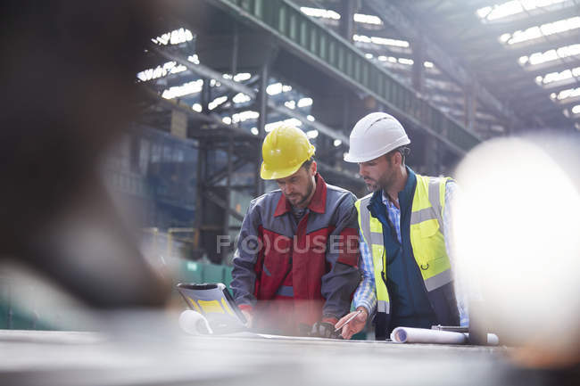 Male engineers using laptop in factory — Stock Photo