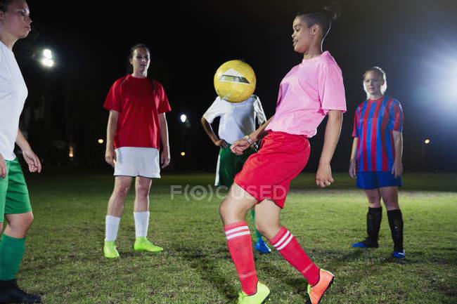 Молода жінка футболістів практикувати на поле вночі — стокове фото