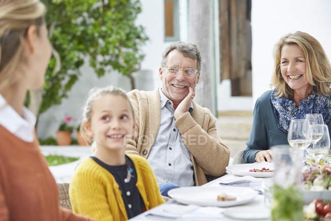 Семья из нескольких поколений наслаждается обедом за столом во внутреннем дворике — стоковое фото