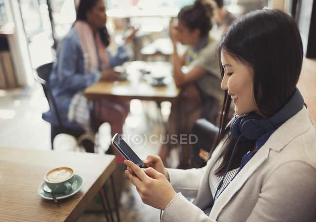 Souriant jeune femme textos avec téléphone portable et boire du café à la table de café — Photo de stock
