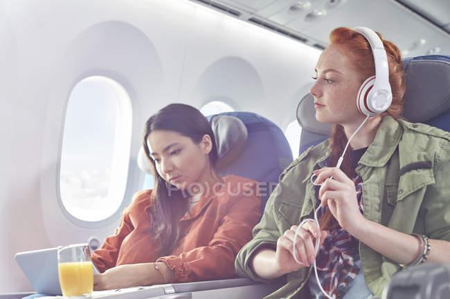 Amigos de mulheres jovens com fones de ouvido e tablet digital no avião — Fotografia de Stock