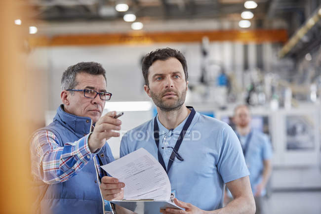 Serious male supervisors with clipboard talking in factory — Stock Photo