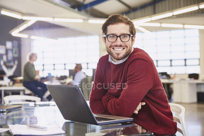 Portrait smiling businesswoman working at laptop in office — Stock Photo