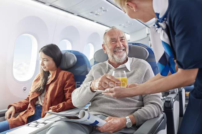 Auxiliar de vuelo que sirven zumo de naranja para hombre en avión - foto de stock