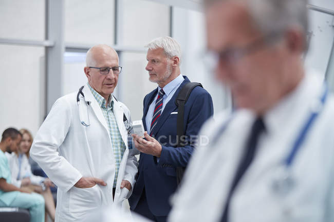 Представитель мужской фармацевтической компании показывает рецепт лекарств врачу в больнице — стоковое фото