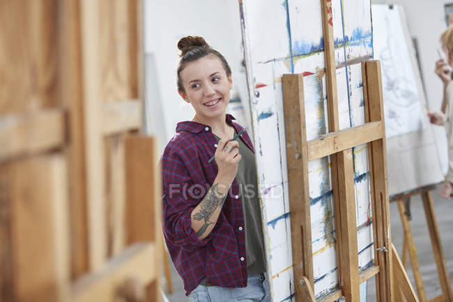 Female artist painting at easel in art class studio — Stock Photo