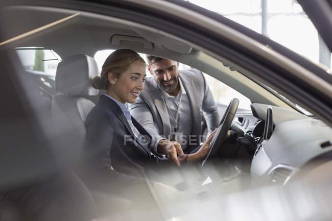 Car salesman explaining new car to female customer in driver?s seat in car dealership showroom — Stock Photo