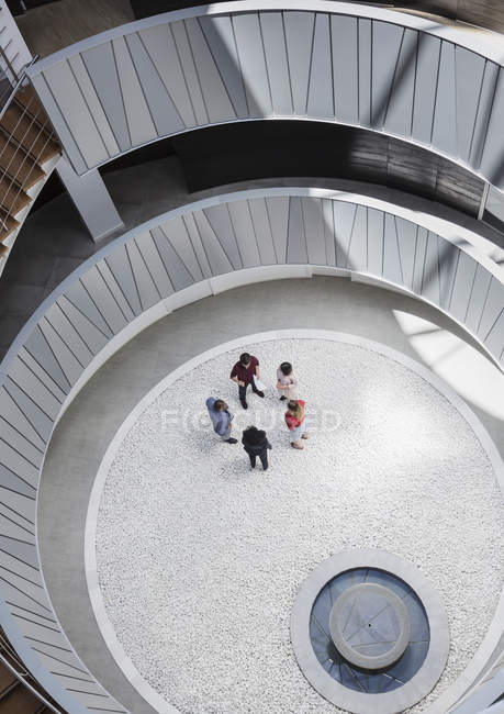 View from above business people talking in round, modern office atrium courtyard — Stock Photo
