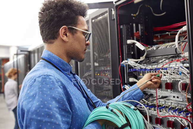 Male IT technician plugging cable into panel in server room — Stock Photo