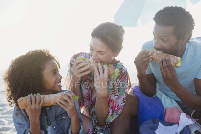 Playful multi-ethnic family eating baguette sandwiches on beach — Stock Photo