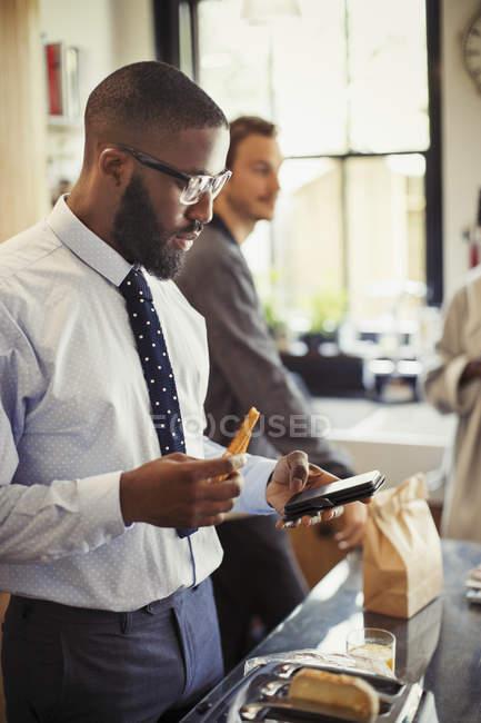Бизнесмен переписывается со смартфоном на кухне — стоковое фото